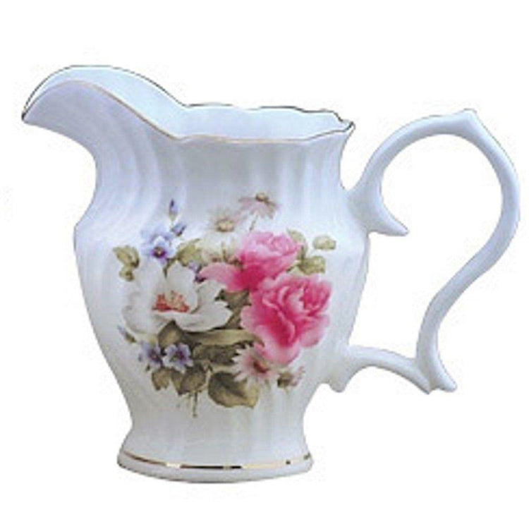 White creamer pitcher Pink, white & blue flowers on front. Trimmed in gold.