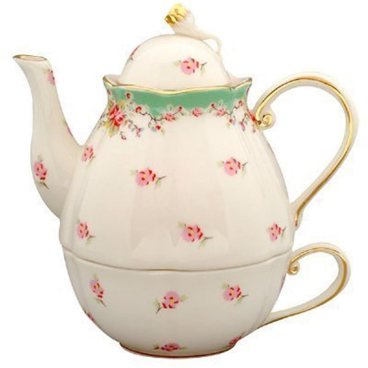 Cream color teapot stacked on tea cup. Small pink flowers over entirety. top of pot is green tinted. Gold trim on pot & cup