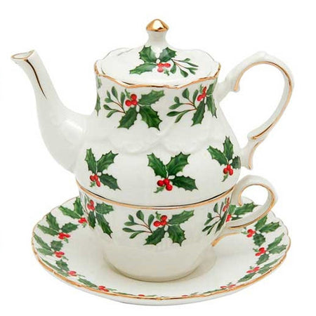 White teapot sitting on cup & saucer, all have holly and berry pattern & gold trim.