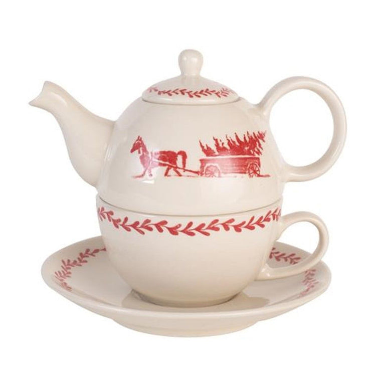 Off white tea for one with saucer.  Red horse and carriage carrying a tree.