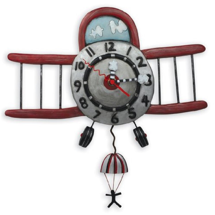Biplane design clock. Clock shows the face of a red biplane with a parachute jumper as the pendulum.