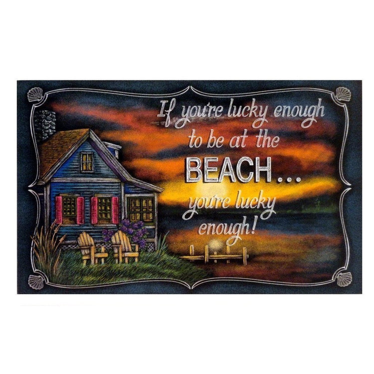 "Black rectangle sign. Text ""If you're lucky enough to be at the beach... you're lucky enough!"" Beach house at sunset image."