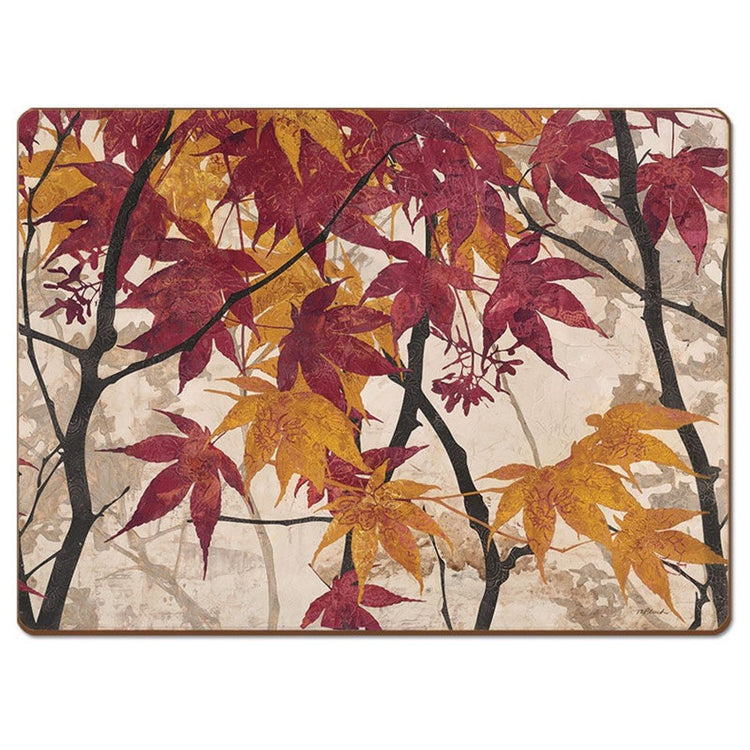 Hardboard placemat showing red and orange leaves on dark brown trees with a cream background.