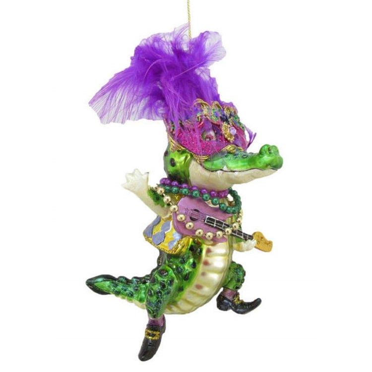 Male crocodile figurine ornament in gold and green holding a guitar with Mardi Gras beads.