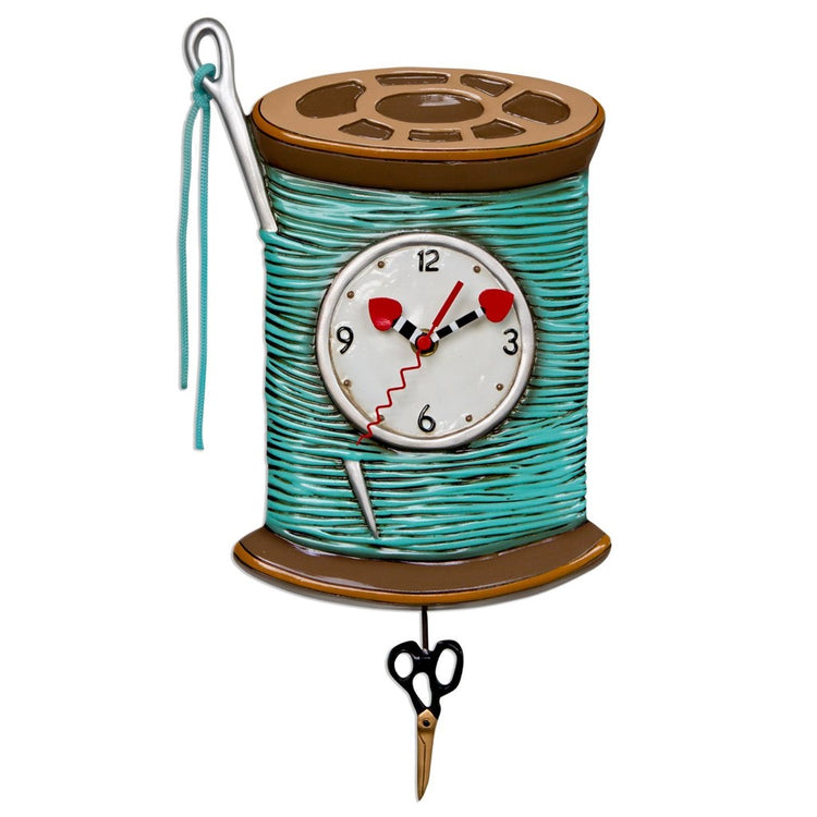 Teal thread with a needle hanging off the side. Red heart hands and black scissor pendulum.