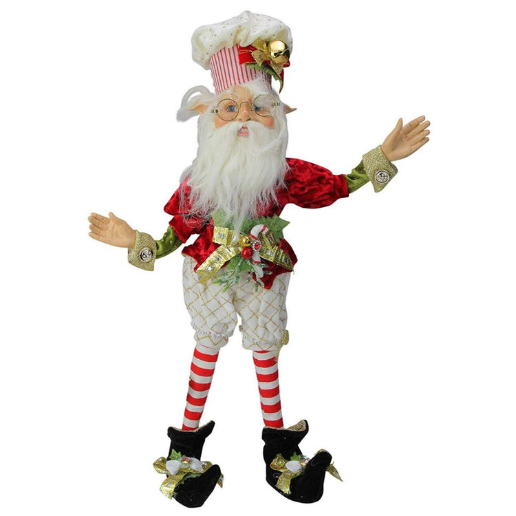 Elf figure with chef hat and red white and green outfit.