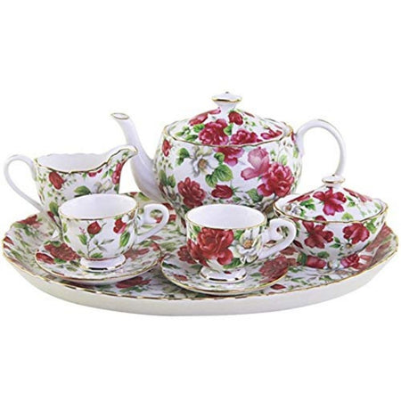White tea set with pink, red & white florals & green leaves.