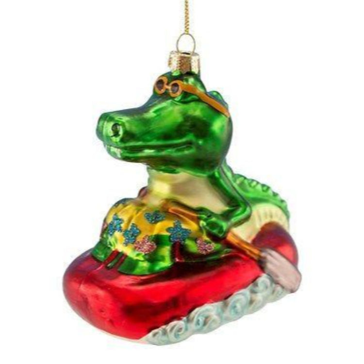 Alligator riding on a raft shaped Christmas ornament. Gator is wearing glasses and holding oars.