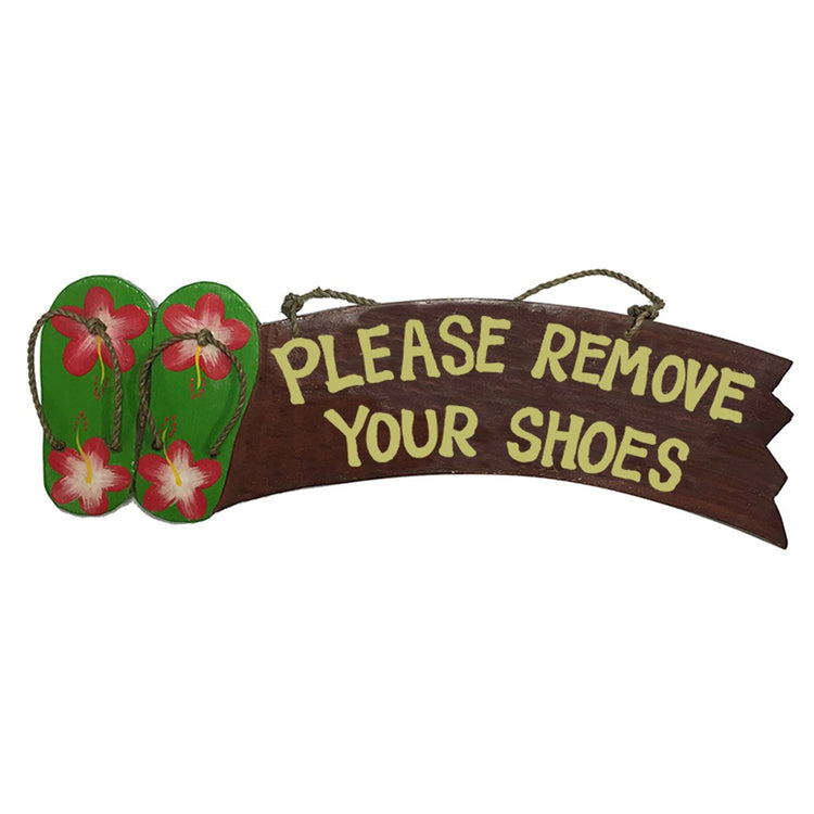 Brown wood sign with green flip flops with pink & white hibiscus. Saying 'please remove your shoes'.
