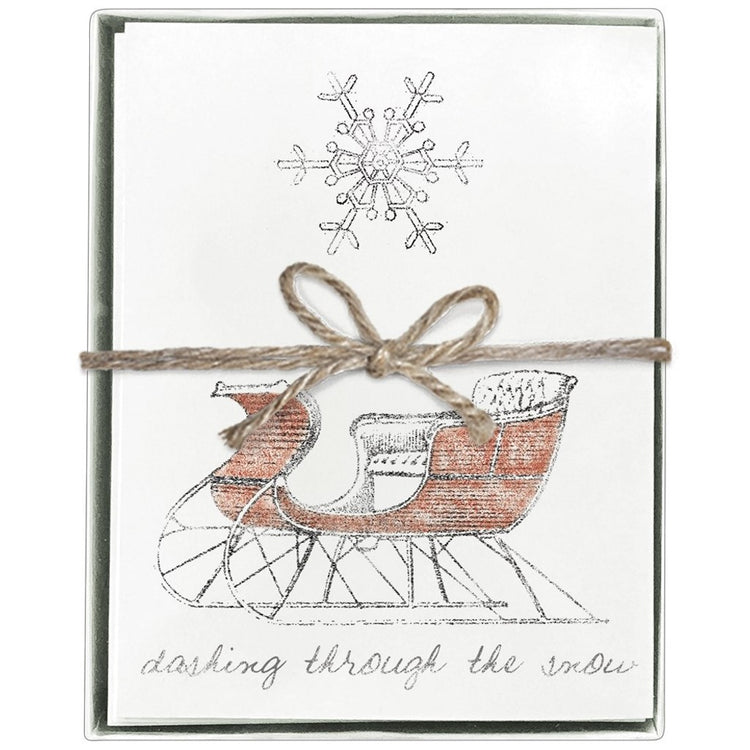"Front view of boxed cards tied with string bow. Large snowflake above red sleigh with text below ""dashing through the snow"""