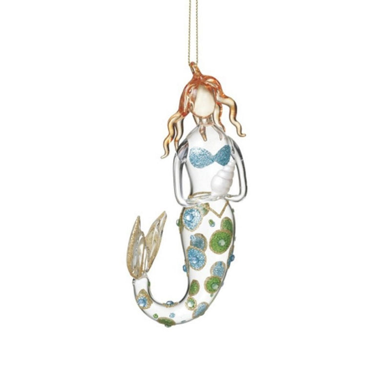 Mermaid figure holding a shell ornament.  Clear glass with blue and green glitter spots.