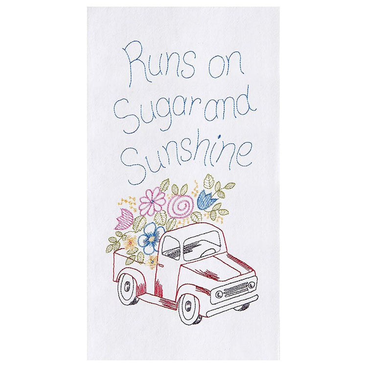 White towel with red truck with blue, yellow, & pink flowers in the bed. Towel says 'Runs on sugar & sunshine'.