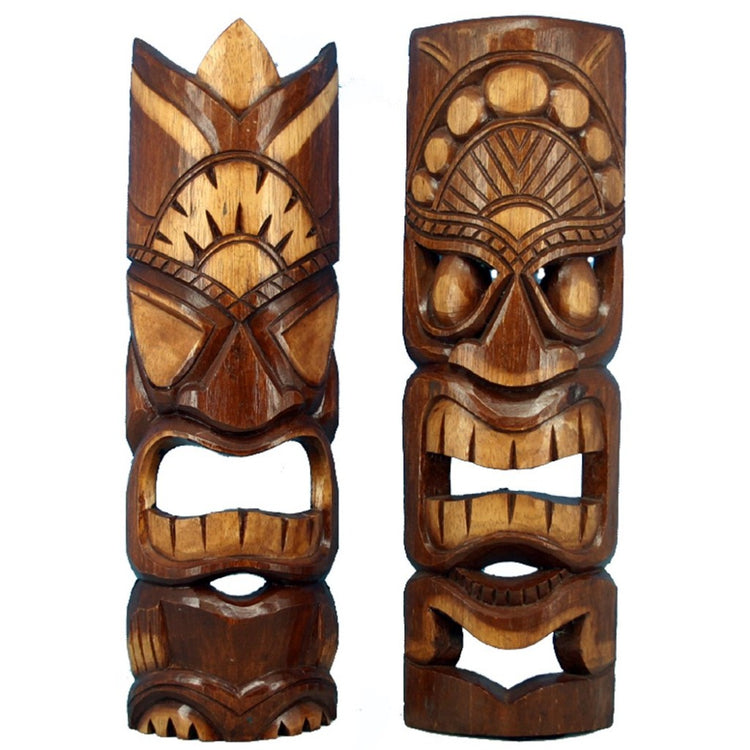 2 carved dark and light brown wood tiki masks.