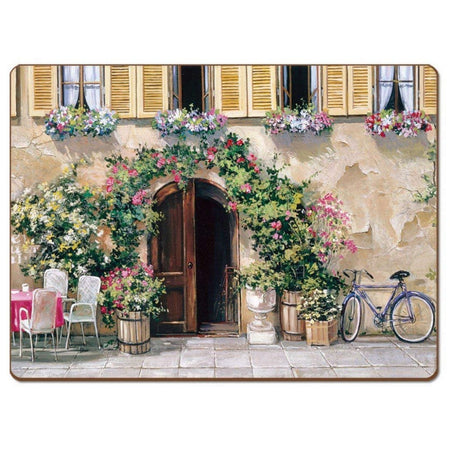 Placemat showing a tan building with 4 windows, a blue bike, a white table for 4, and lots of pink and white flowers.
