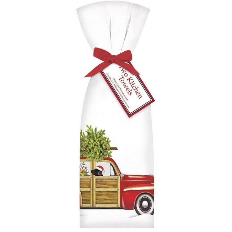 2 white towels tied with red ribbon. Towel shows red and wood station wagon with black dog, presents & tree.