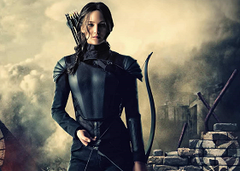 Katniss Everdeen walking with Mockingjay symbol graffitid behind her