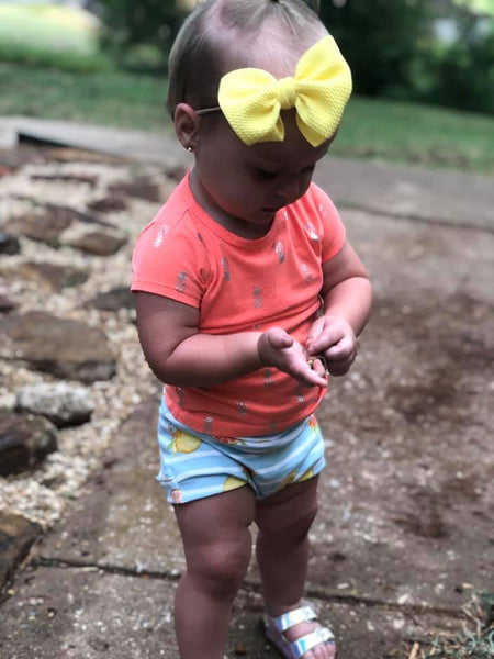 baby playing in citrus shorts
