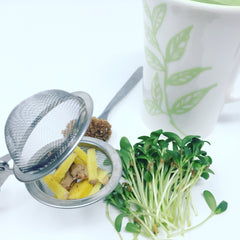 Ingredients of fenugreek microgreens tea including ginger, sugar, and fenugreek microgreens.