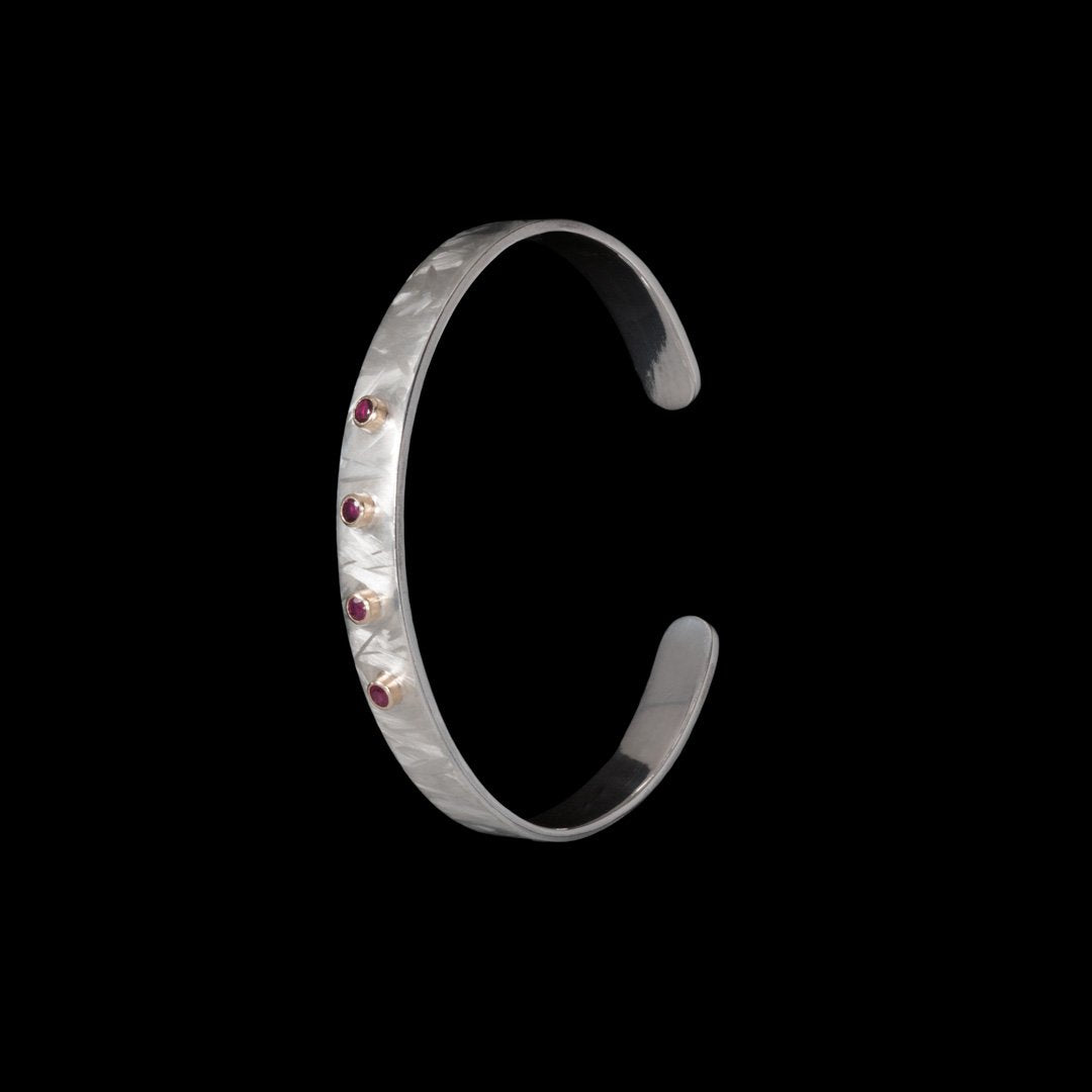 Solid silver bangle with gold mounts for 4 Ruby's.  Hallmarked with our jewellery maker's mark.  Contact NI Silver for any jewellery commissions.