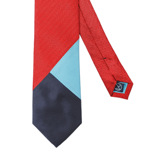 Three-piece necktie combining a main red herringbone with light blue and navy.