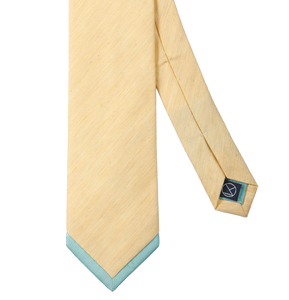 A matt yellow necktie with a turquoise pointed tip.