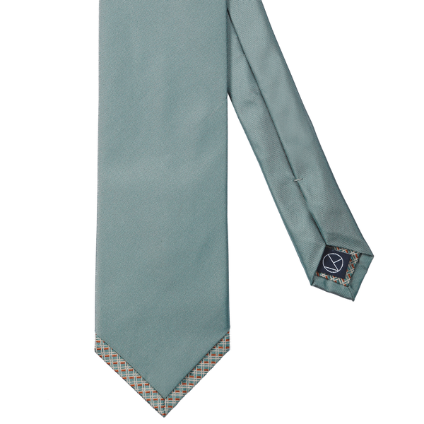 A solid turquoise necktie with a patterned turquoise and caramel silk pointed tip.