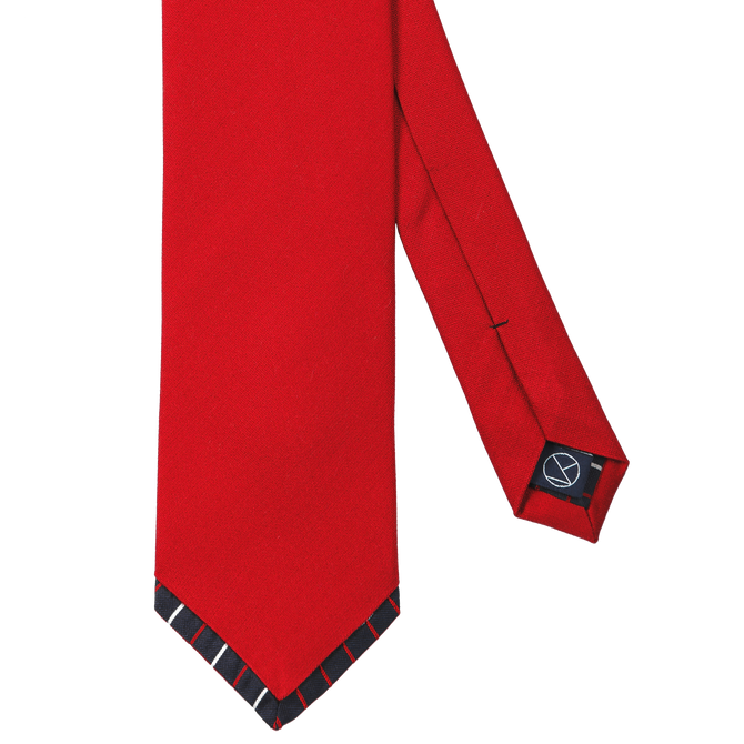 A matte red necktie combined with a checked navy pointed tip.