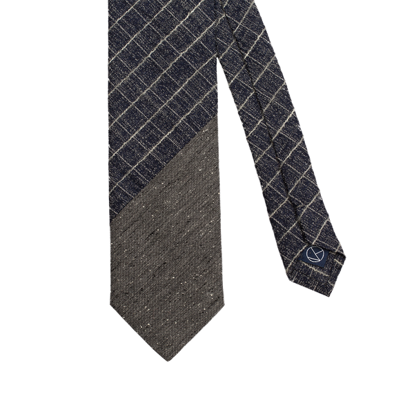 Two-piece tie combining a warm blue fabric with a gridded silver pattern, and a textured gray fabric.