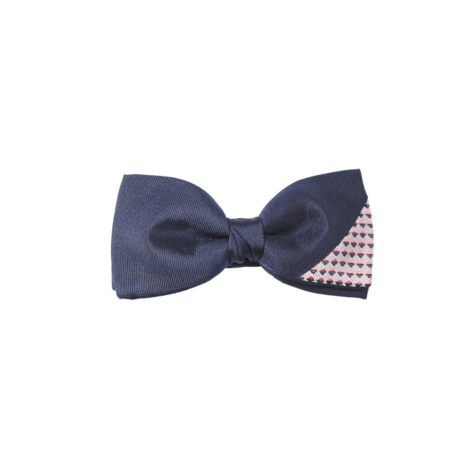 An elegant and soft navy bowtie combined with a dapper piece of navy and pink patterned silk on the corner.