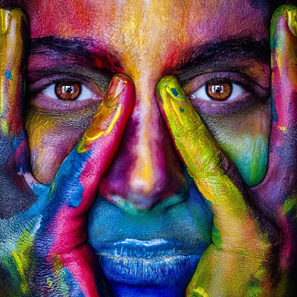ONE simple step to improve your sleep and ultimately take your life to the next level - image of a face covered in many different colours paint