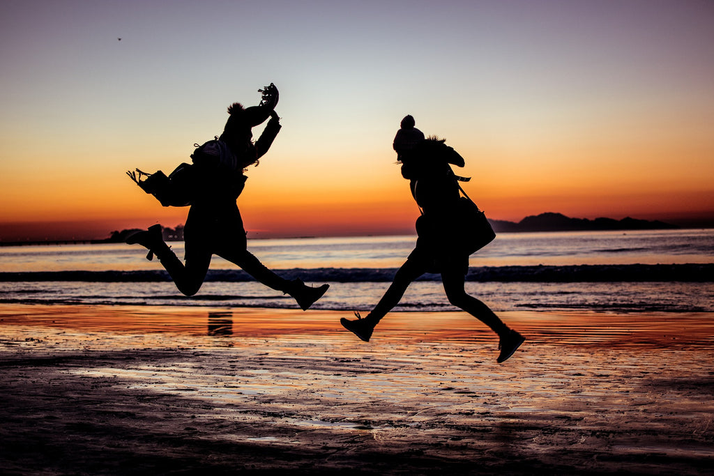 ONE simple step to improve your sleep and ultimately take your life to the next level - image of two people jumping high and being happy
