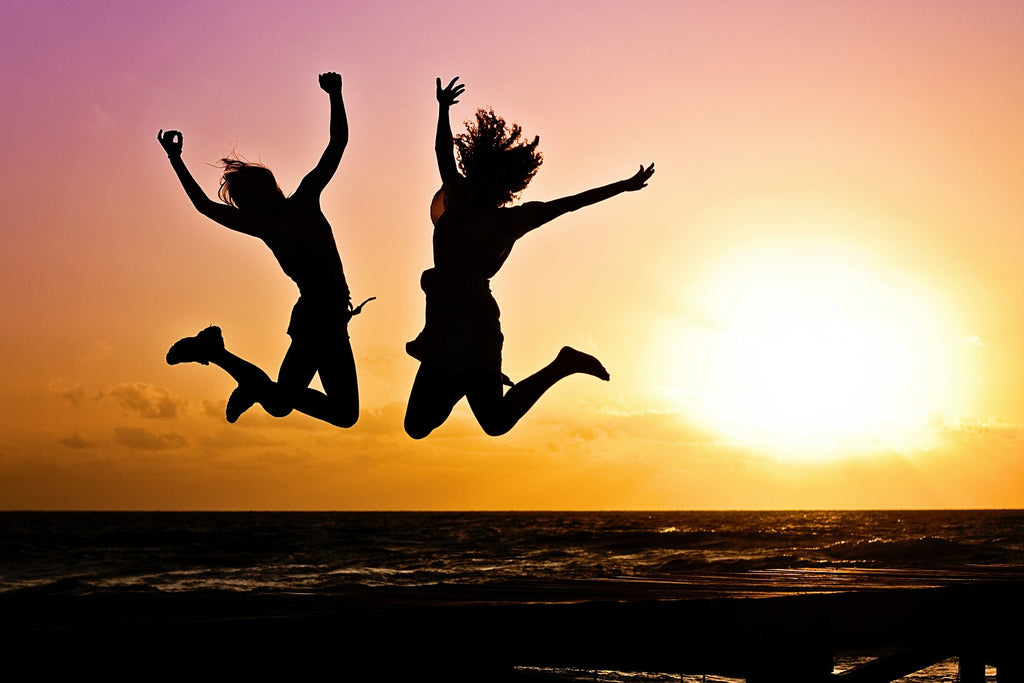 Two friends in joy with sunsetting behind