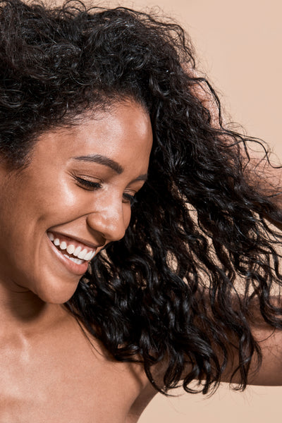 beautiful young woman with dark curly hair smiling
