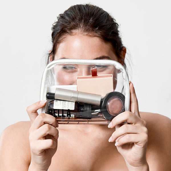 young brunette woman holding a Beysis transparent makeup case filled with cosmetics