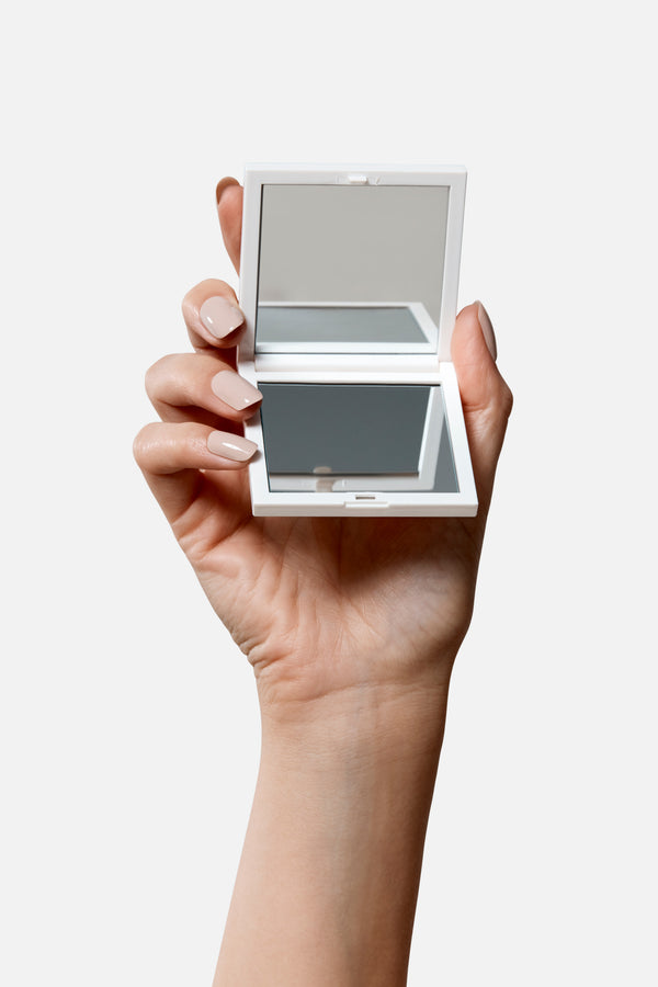 Woman's hand holding a white compact makeup mirror