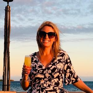 Picture of a young woman drink champagne at sunset