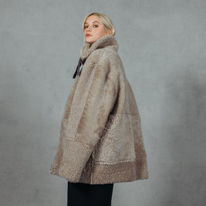 Black Beige. Shearling. Reversible. Fits comfortably across the shoulders, loose-fit through the torso. Relaxed armholes. 32 inch length