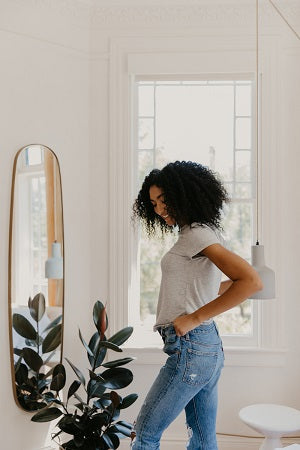 Young woman trying pair of jeans in front of a mirror