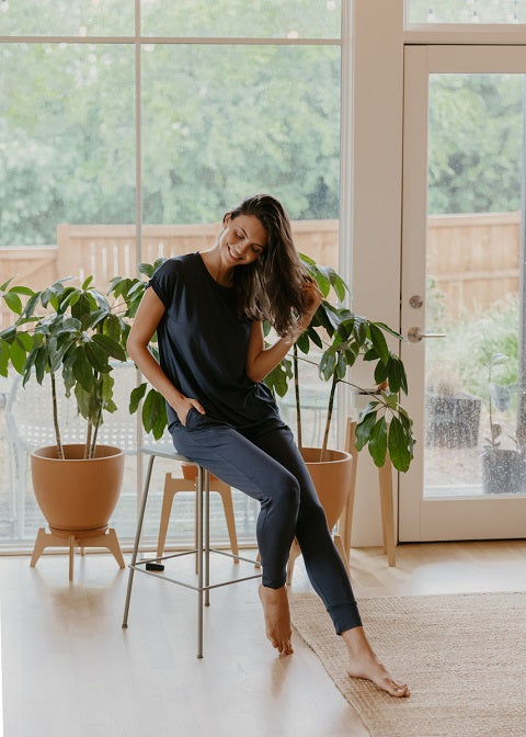 Woman sitting on a high chair, wearing dark blue joggers and matching shirt