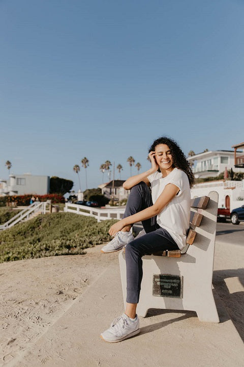 Happy young woman siting on a bench dressed in joggers and t-shirt