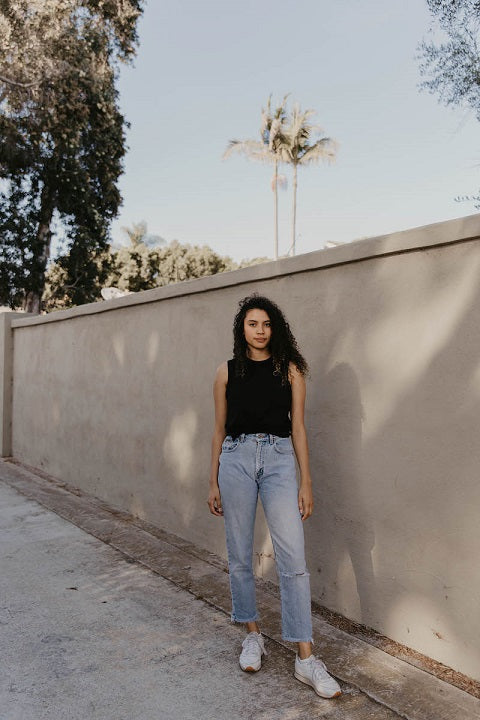 Young woman in jeans and athletic shirt standing next to a wall