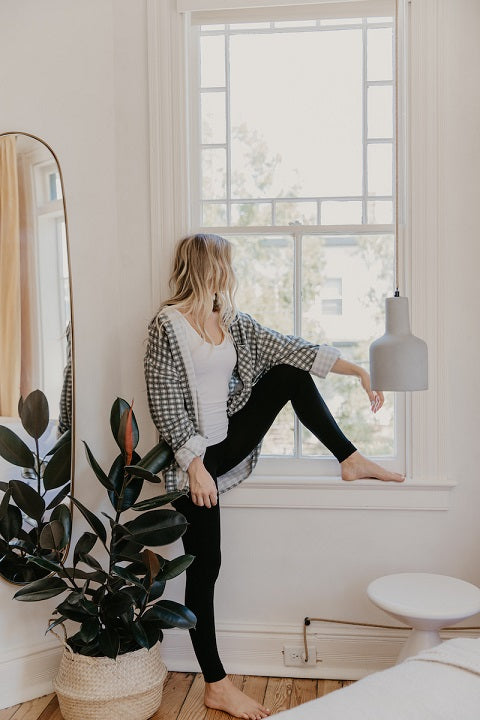 Relaxed woman in loungewear leaning against the window