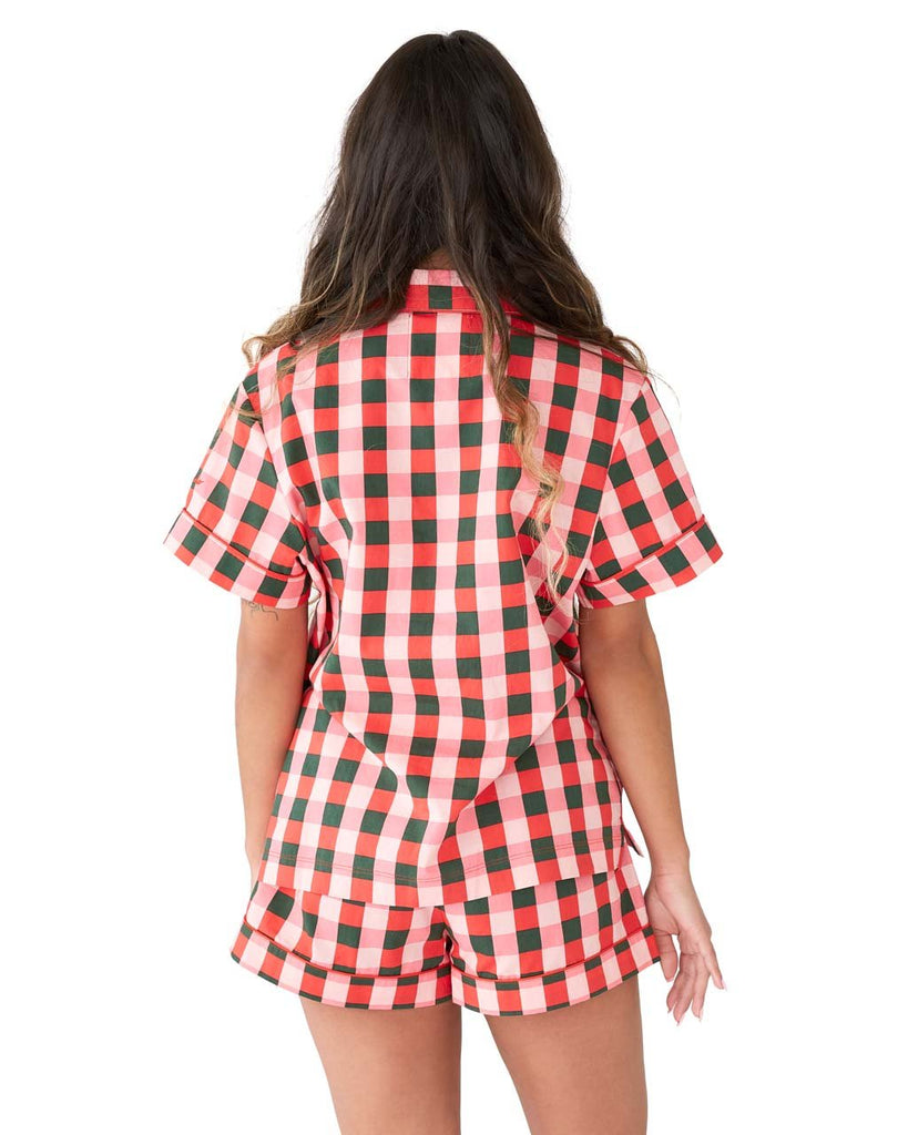 Back shot of woman in a short sleeve green & pink plaid button down pajama top.