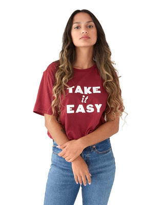 Woman in a dark red tee with white lettering Take It Easy, pink fanny pack, and black pants.
