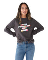 Woman in a long sleeve vintage black sweatshirt with a rainbow graphic Look Forward Not Back in the center.