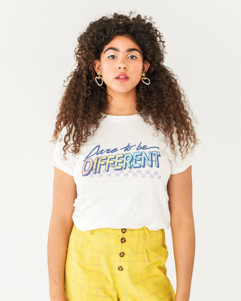 "Model wearing short sleeve white ""Dare to Be Different"" tee with yellow pants"