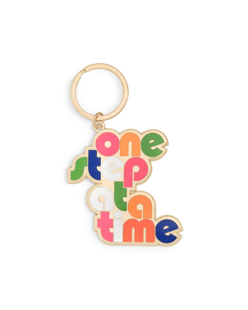 gold keychain with the words one step at a time