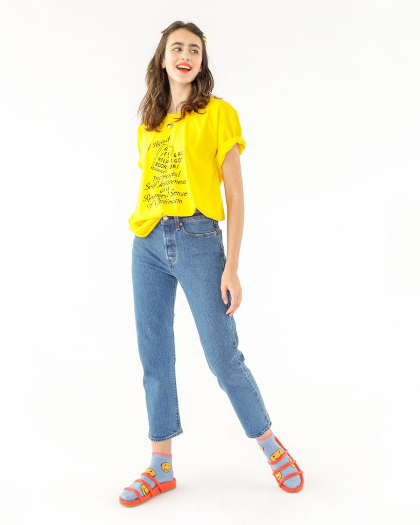"Woman in jeans and a yellow short sleeve tee with a black graphic that reads ""I read a self help book & all I got was increased self-awareness & a renewed sense of optimism."""