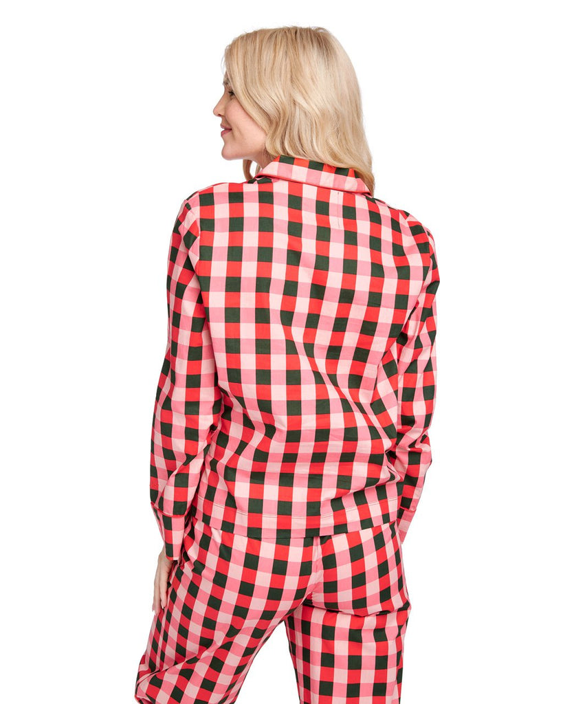 Back shot of woman in a long sleeve green & pink plaid pajama top.