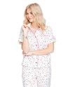 Woman in a short sleeve button down pajama top with allover multi-color polka dots.